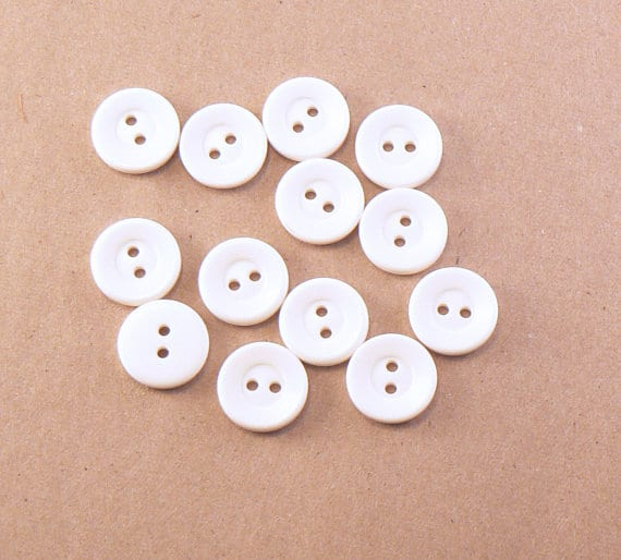 White plastic buttons with two holes.