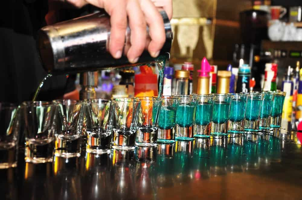 Barista pouring alcohol on a row of shot glasses.