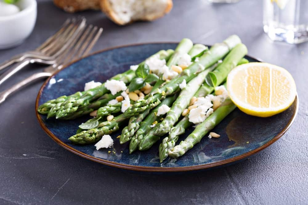 A plate of asparagus with a slice of lemon.