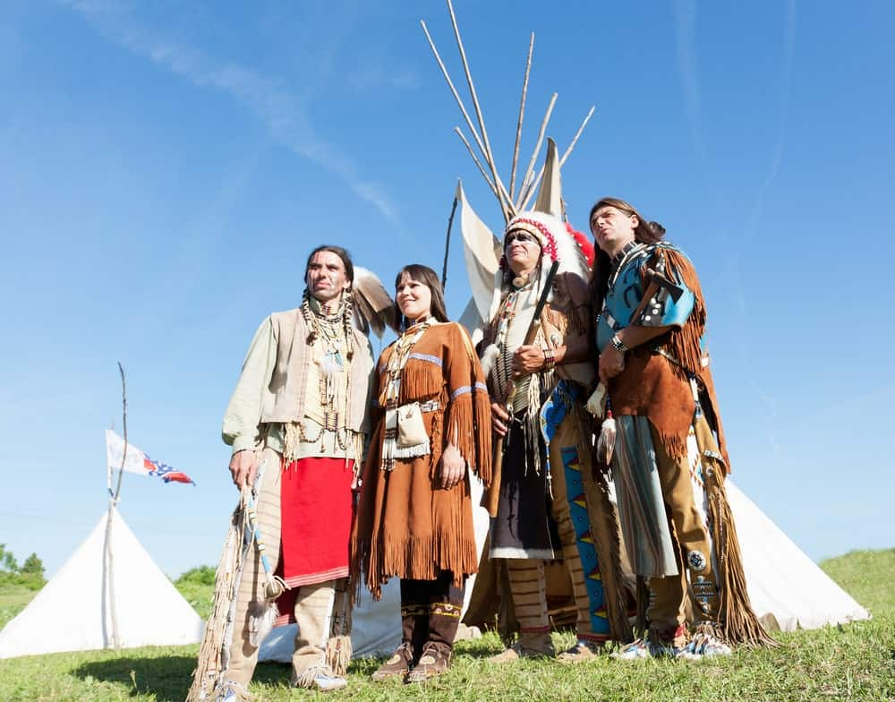 Members of the Native American tribe stand inf front of a wigwam.