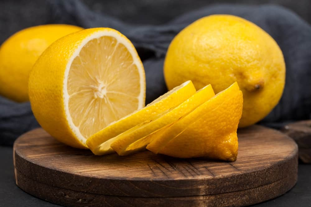 Whole pieces and slices of Bearss Lemons on chopping board.