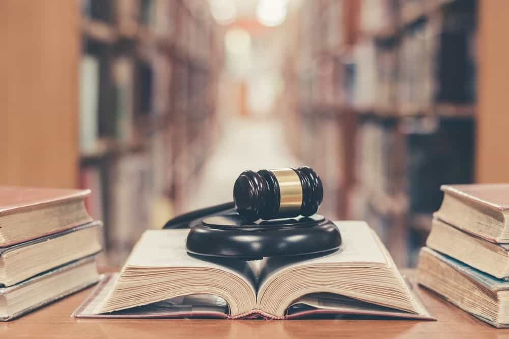An open book with a judge's black gavel on top is flanked by a trio of stacked hardbound books on wooden desk in a library.
