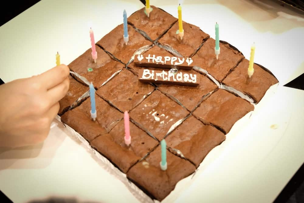 Brownies with birthday candles and a Happy Birthday greeting.