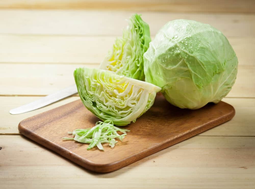 A whole cabbage and two pieces of chopped cabbage in half with some strips on wooden chopping board.