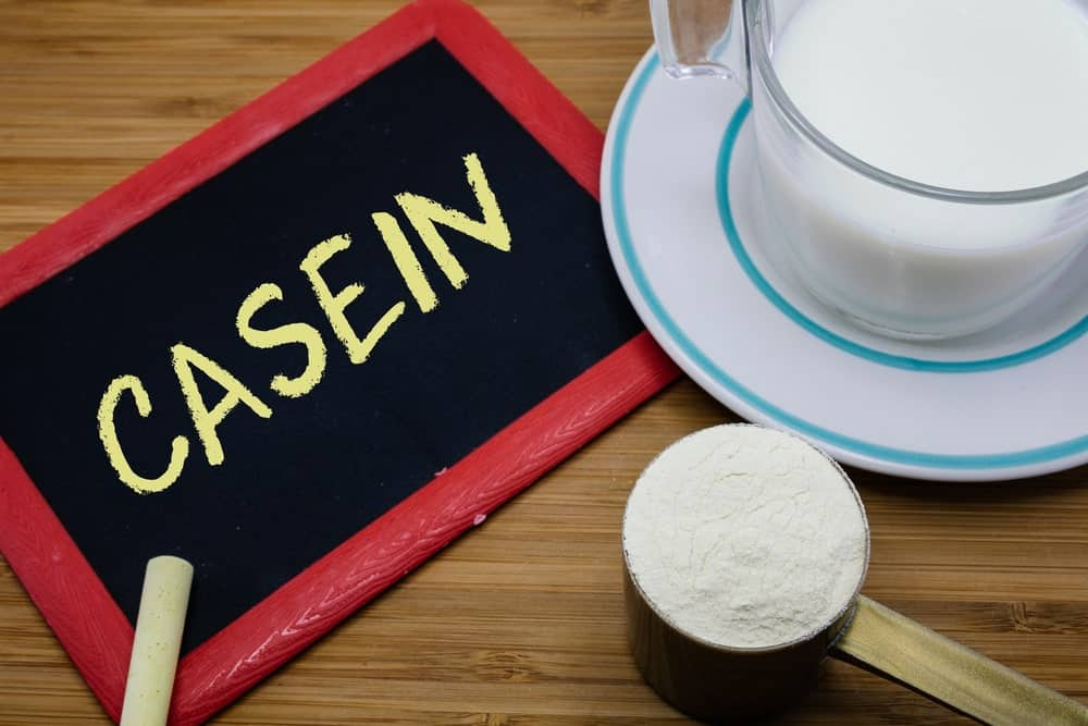 Casein protein powder on a scoop beside a glass of milk on saucer and a board with the word Casein written on it.