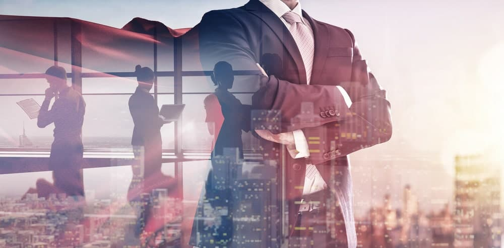 A businessman in suit and red cape has his hands folded across his chest as he faces the city skyline with reflections of employees working at the building.