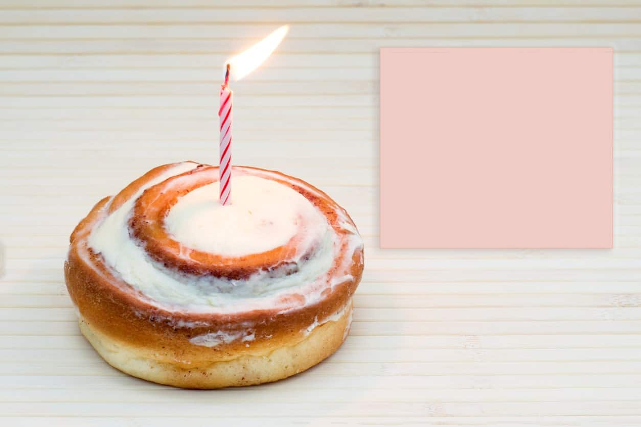 Cinnamon roll cake with a candle beside an empty sticky note on wood background.