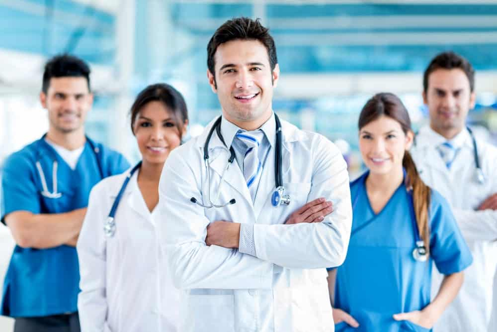 Medical professionals make a V-formation as they stand smiling at the camera.