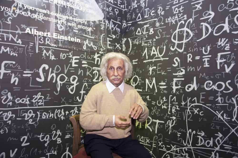 Wax statue of Albert Einstein with chalked scribbles of mathematical equations as background.