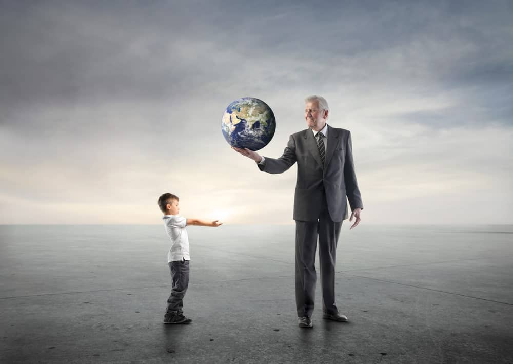 An old man holds the Earth in his hand while a young boy extends his arms to catch it.