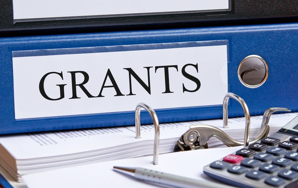 "The word ""Grants"" in caps lock letters printed on white paper and taped on a blue book on top of papers with a calculator and a pen beside it."