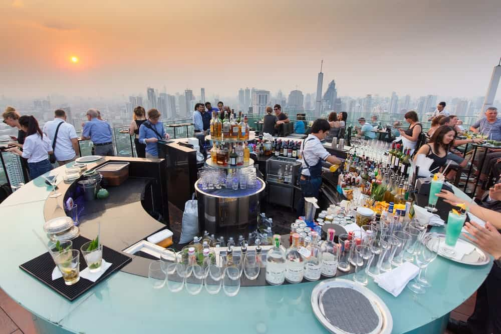 A luxury rooftop bar with customers enjoying the cityline and the sunset.