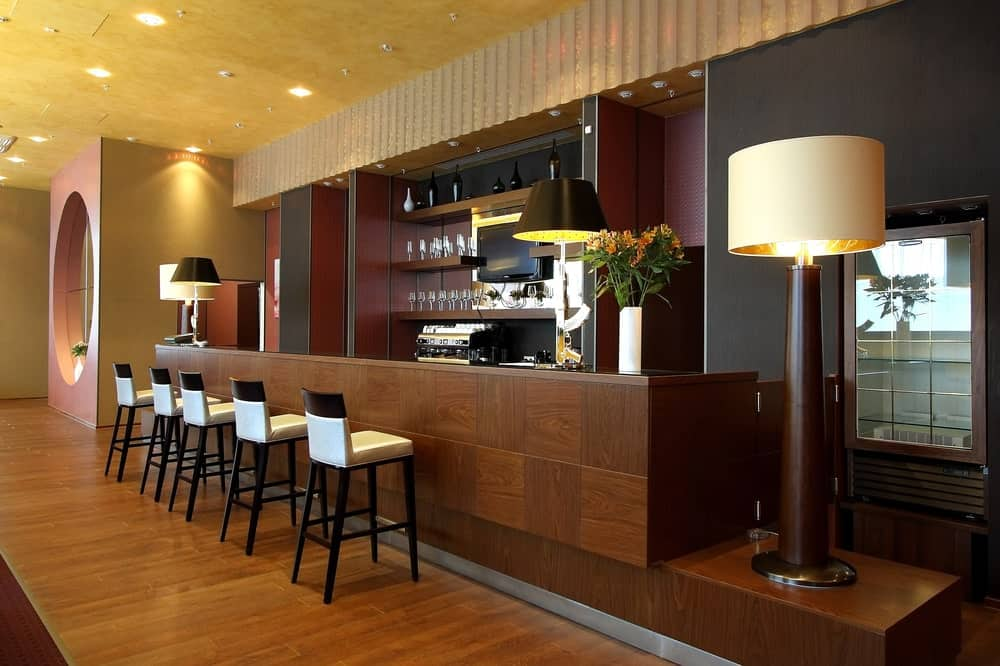 Hotel bar with wood bar counter, wood flooring, sleek bar chairs, and large floor lamp.