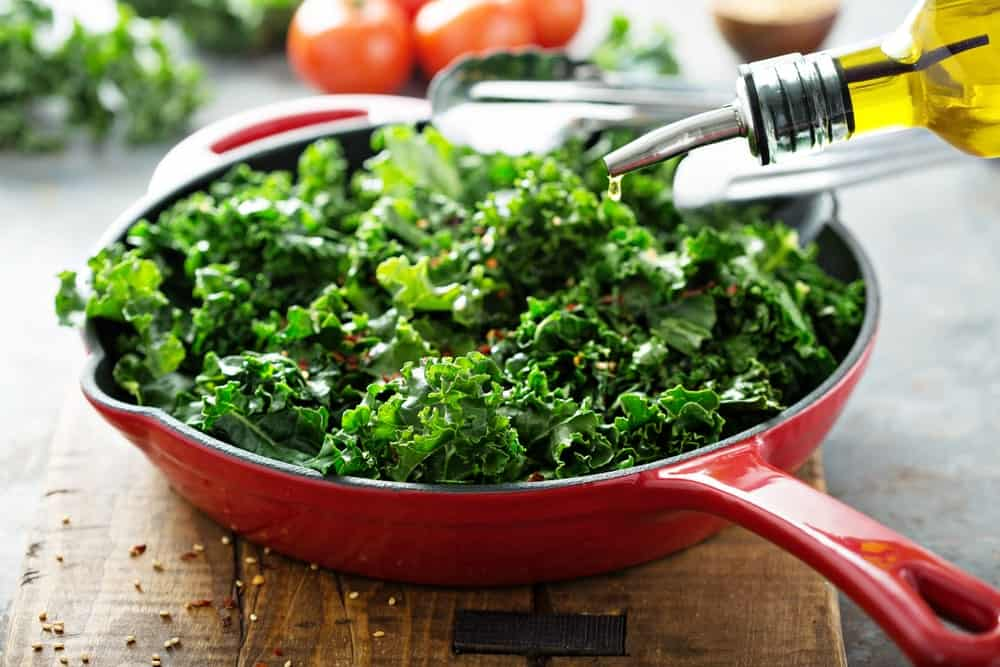 Sprinkling olive oil on kale in a red pan.