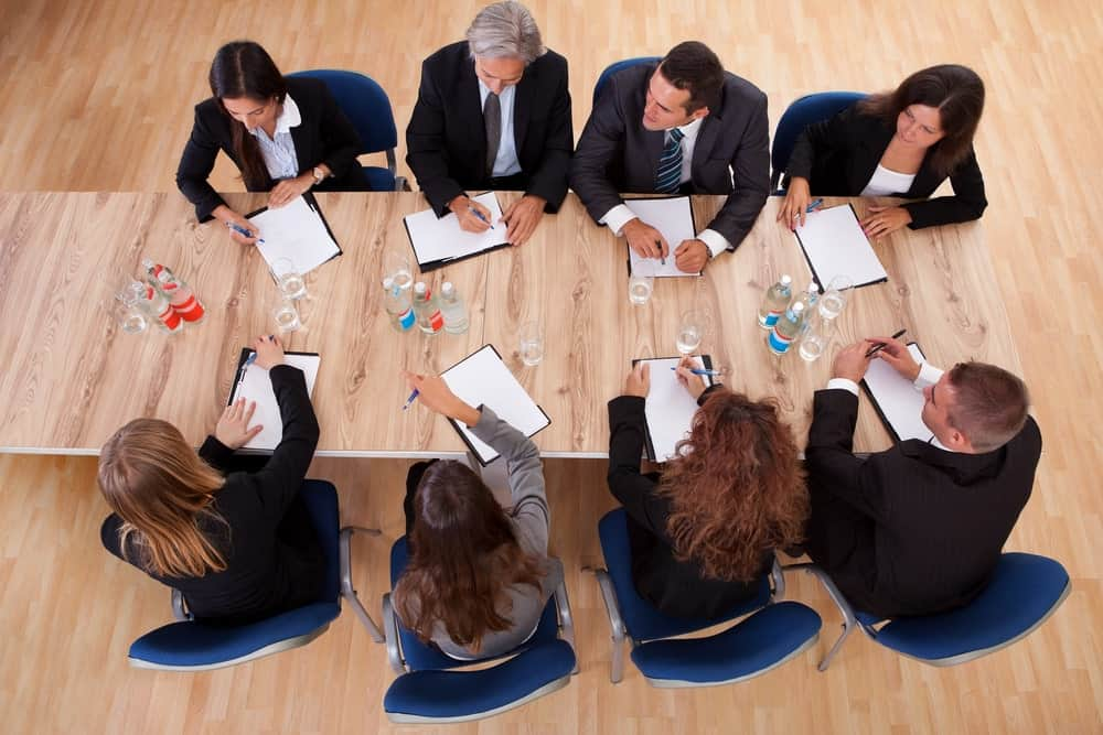 A team of board of directors huddle over a meeting with papers, pens, glasses, and mineral bottles on wooden desk standing on wooden flooring.