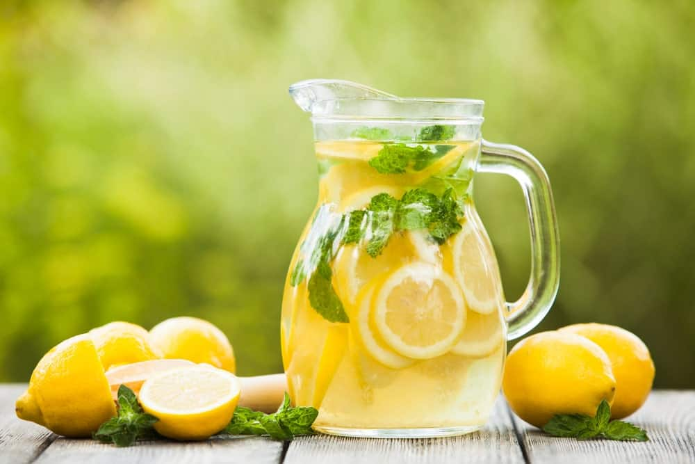 A pitcher of lemonade and lemons on wooden desk.