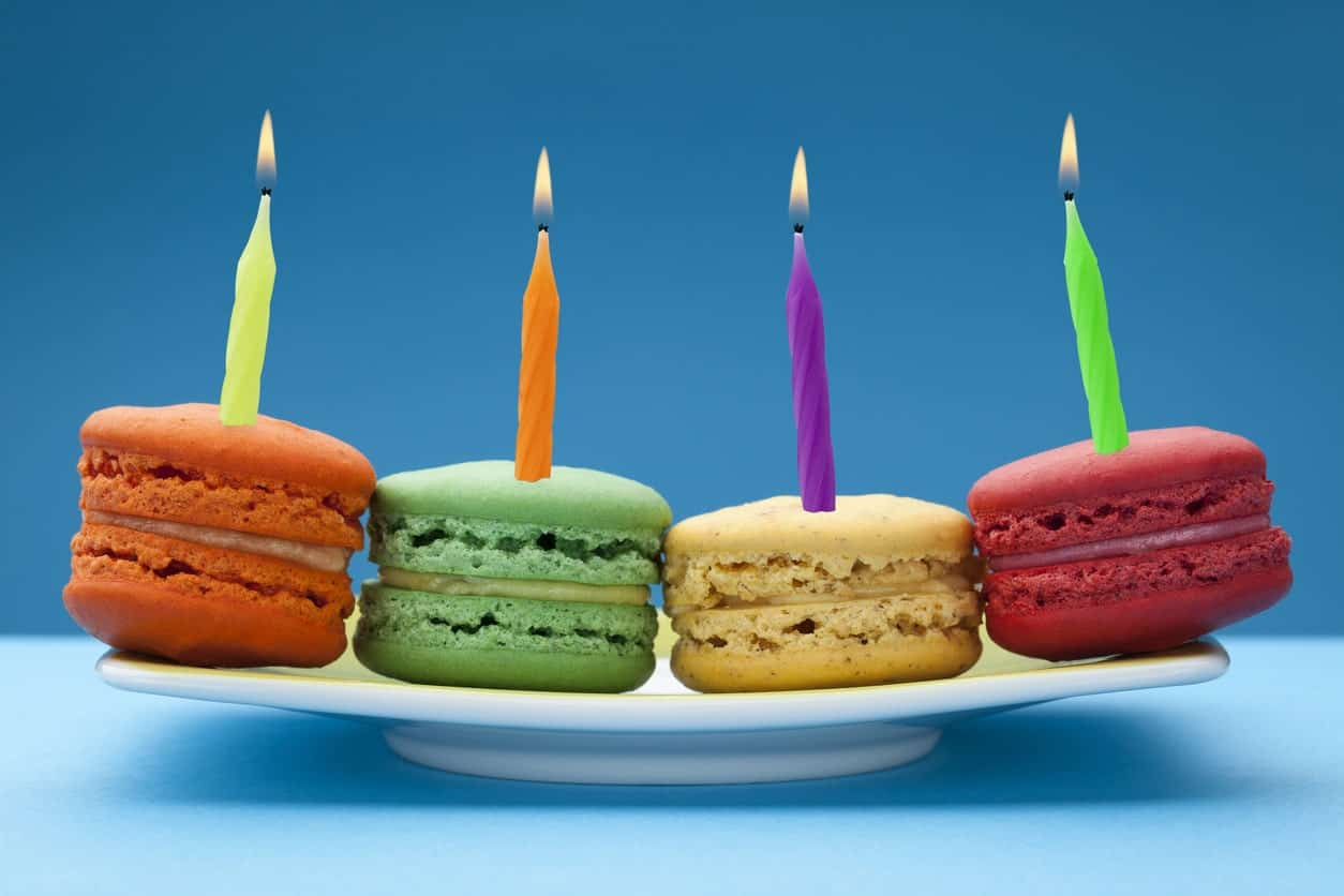 Colorful macaroons with birthday candles on a white plate against blue background.