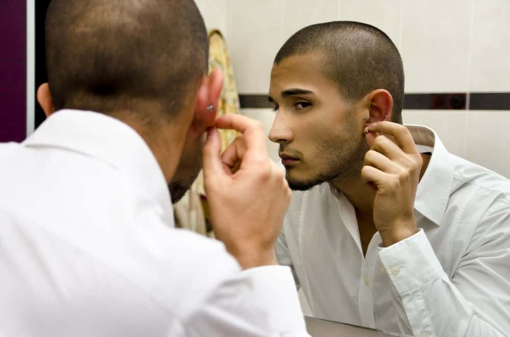 Handsome male model checking out his earrings on the mirror.