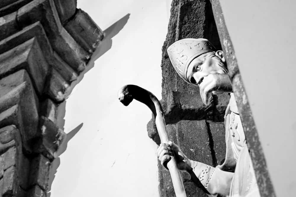 Statue of priest and stone structure in black and white.