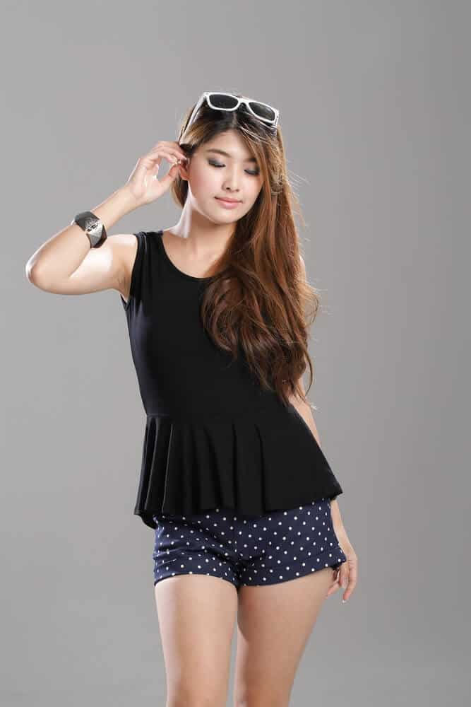 Model wearing a black peplum top.