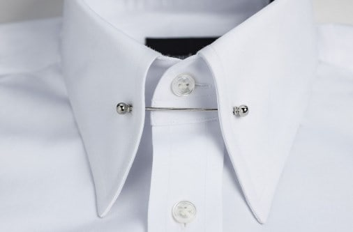 Closeup of a white shirt with pin tie.