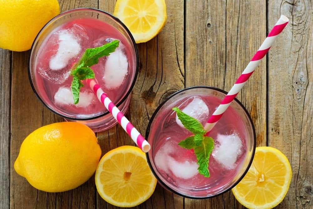 Two glasses of pink lemonade with pink striped straws beside lemons on wooden background.