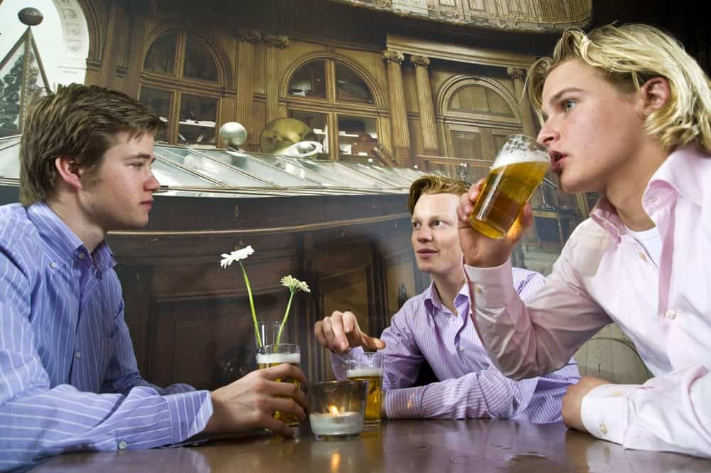 Three young men each with a glass of beer at a table in a bar.