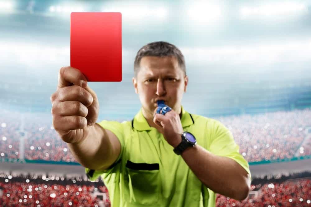 A soccer referee wearing a green polo shirt blows on his whistle and raises a red card in front of him with the packed stadium as the background.