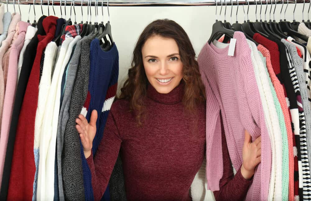 Woman peeking from a rack of different tops.