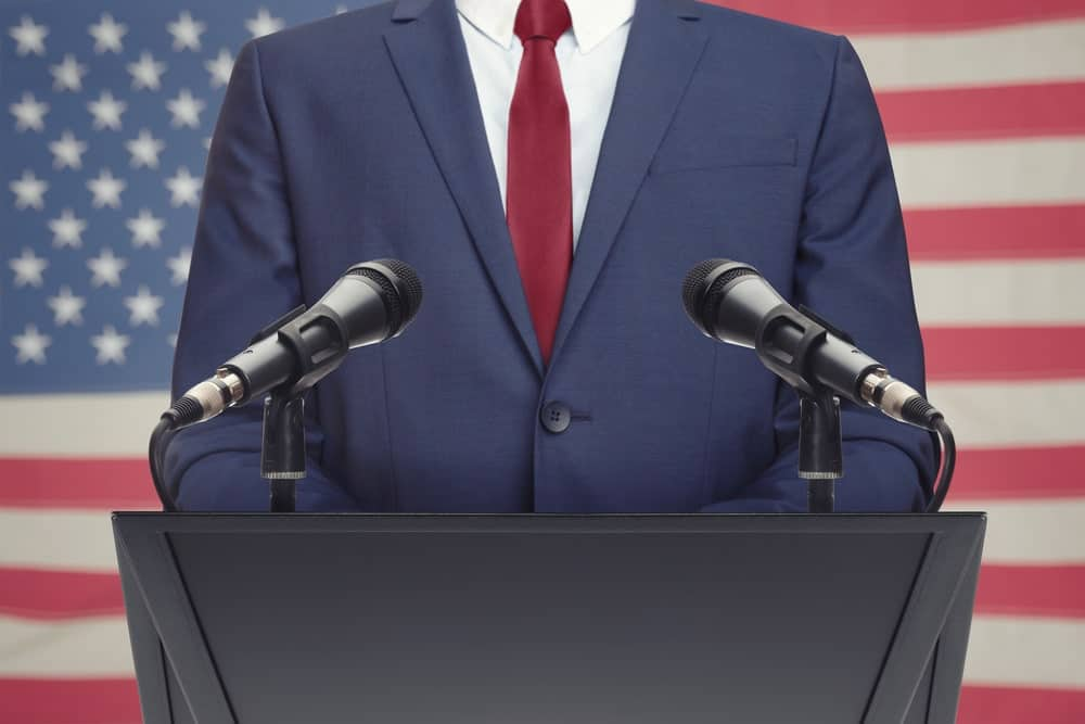 A man in suit stands in front of two microphones on a podium with the flag of the USA blurred on the background.
