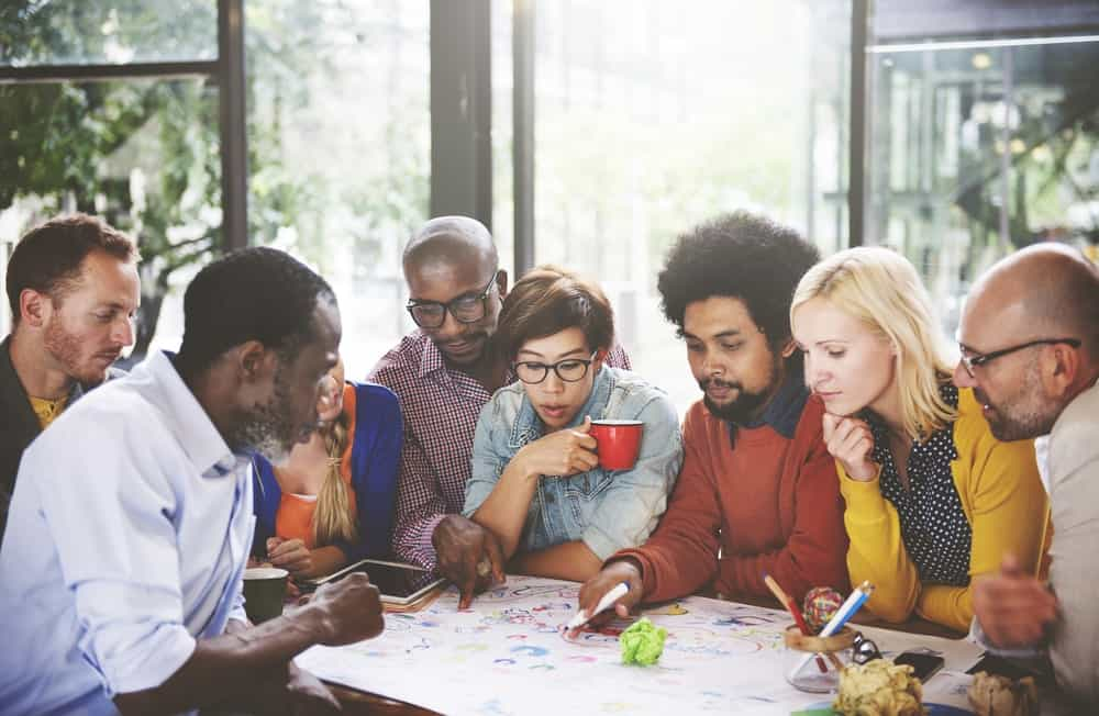 A team of multi-ethnic employees huddles at a table as they stare down at a large white paper with scribbles.