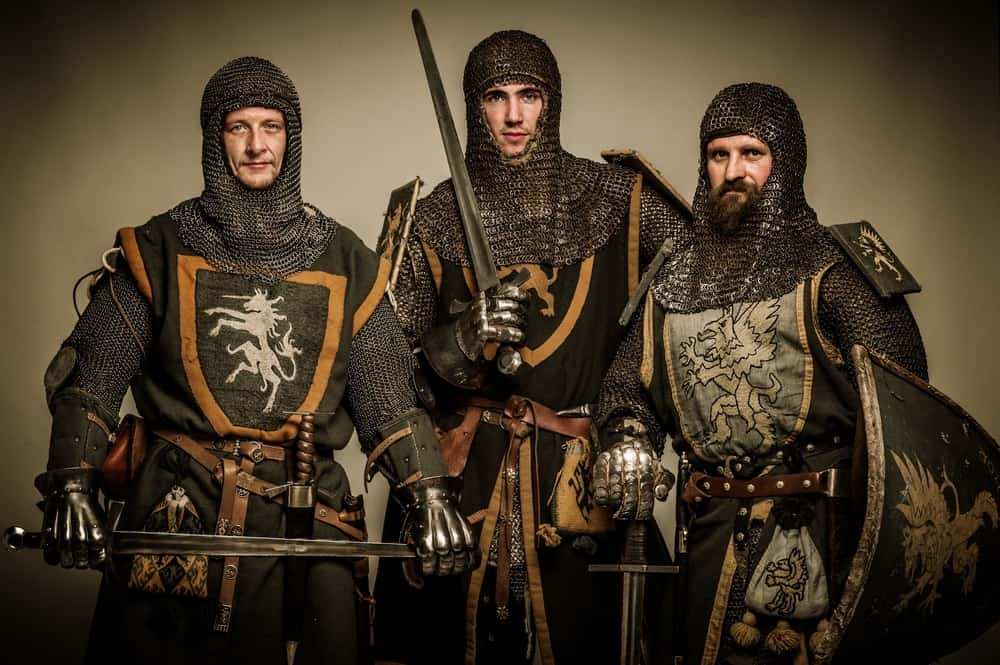 Three men in full medieval knight gear.