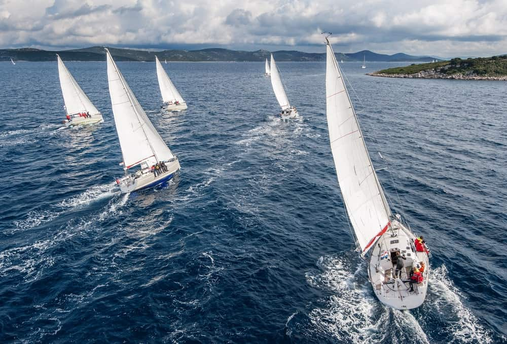 A group of sailors participate in a sailing event.
