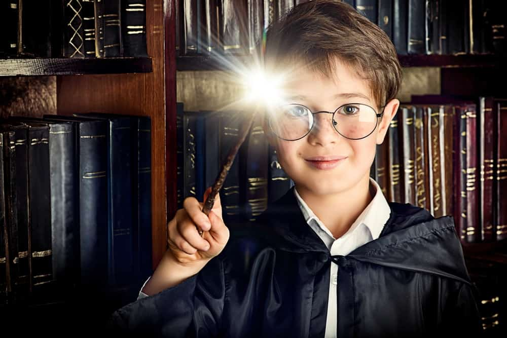 A boy holds an illuminating wand to perform some magic.