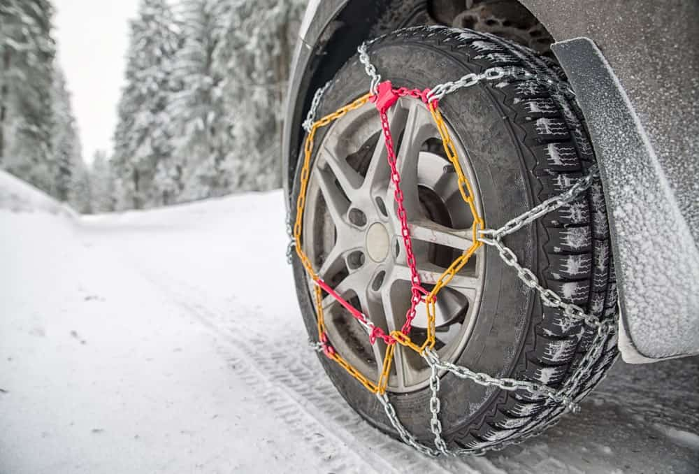 Snow chains on a tire on a snowy road.
