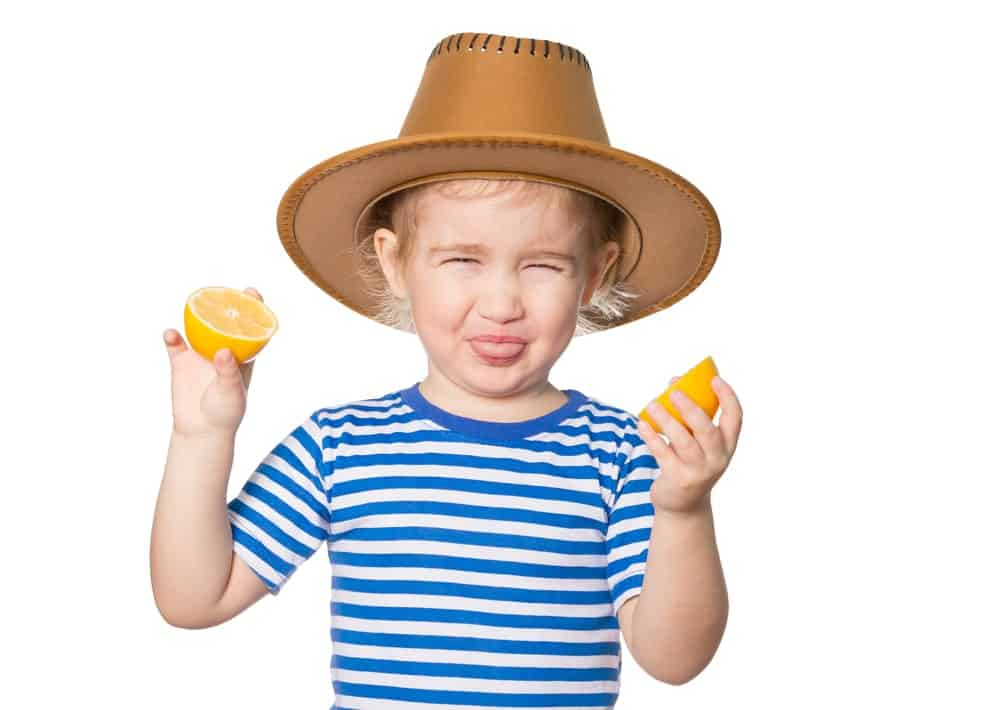 Child showing a sour face while holding sliced lemons.
