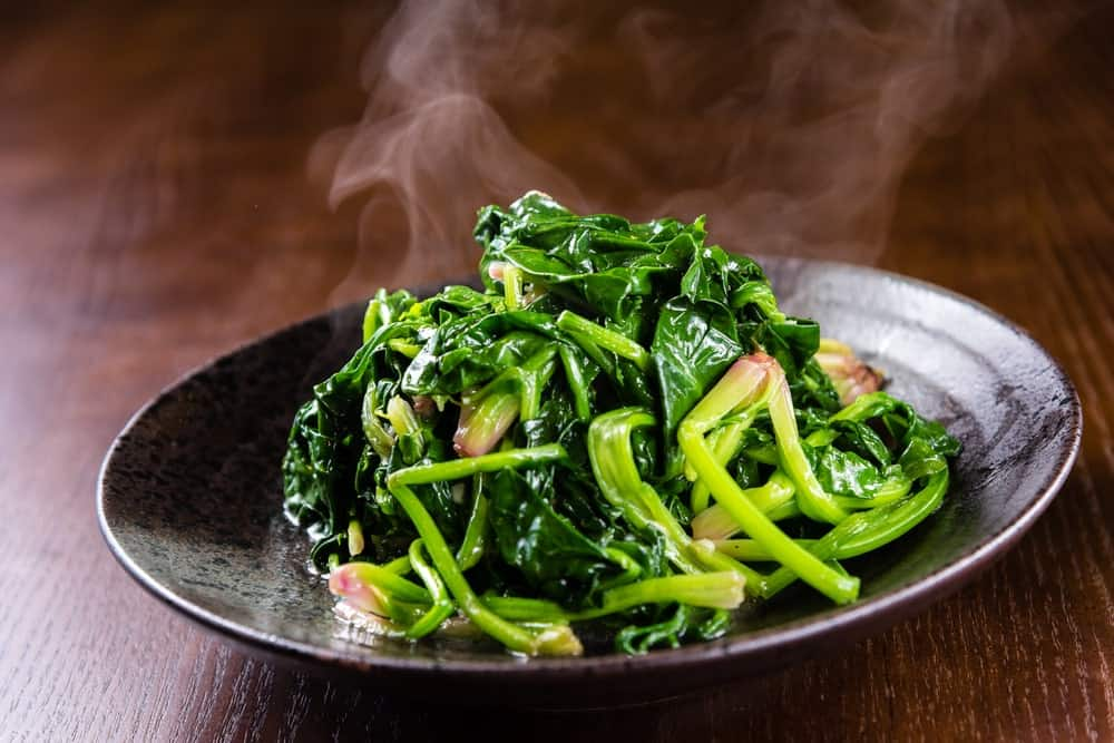 Steaming fried spinach in a black plate on wooden background.