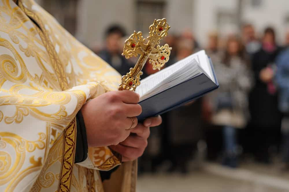 Closeup of a bishop in gilted robe carrying a golden cross on one hand and an open Bible on the other.