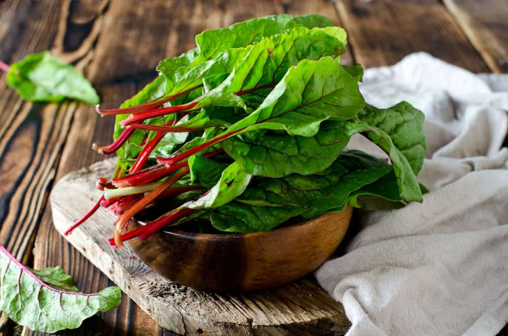 Swiss chard on wooden bowl on wooden chopping board and white cloth on wooden background.
