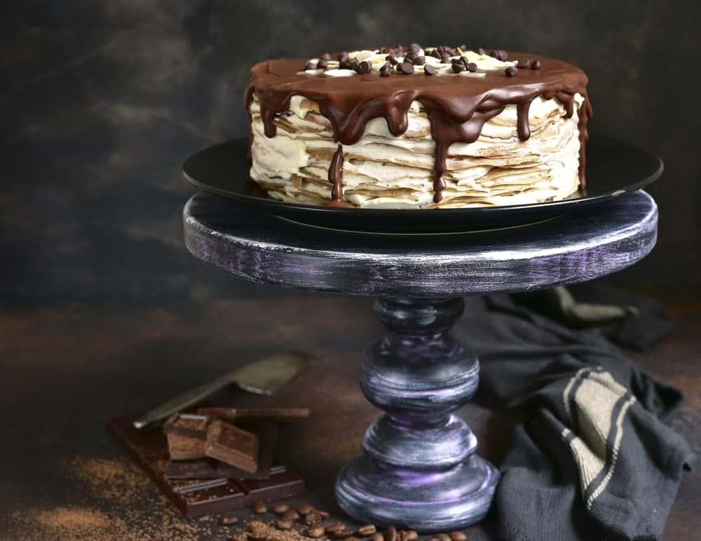 Tiramisu crepe cake on cake tray against gray background.