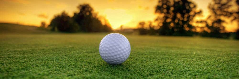 Golf ball on golf course at sunset