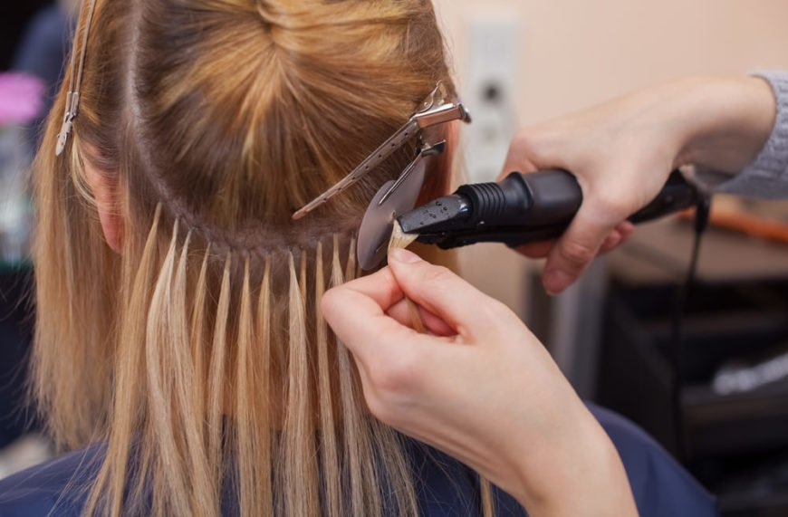 Hairdresser applying hair extensions to blonde client