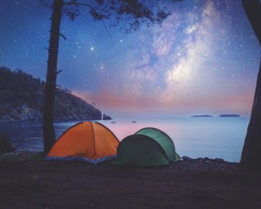 Tent camping on shore at night