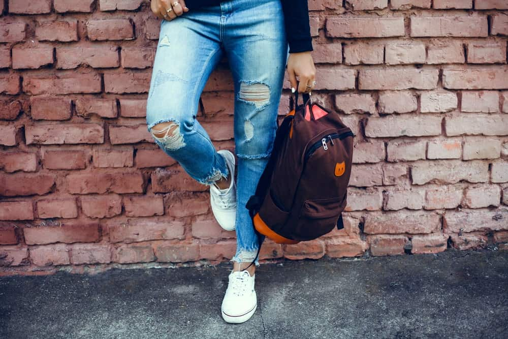 Person in tattered jeans and white sneakers clutching a backpack in one hand while leaning against a brick wall.