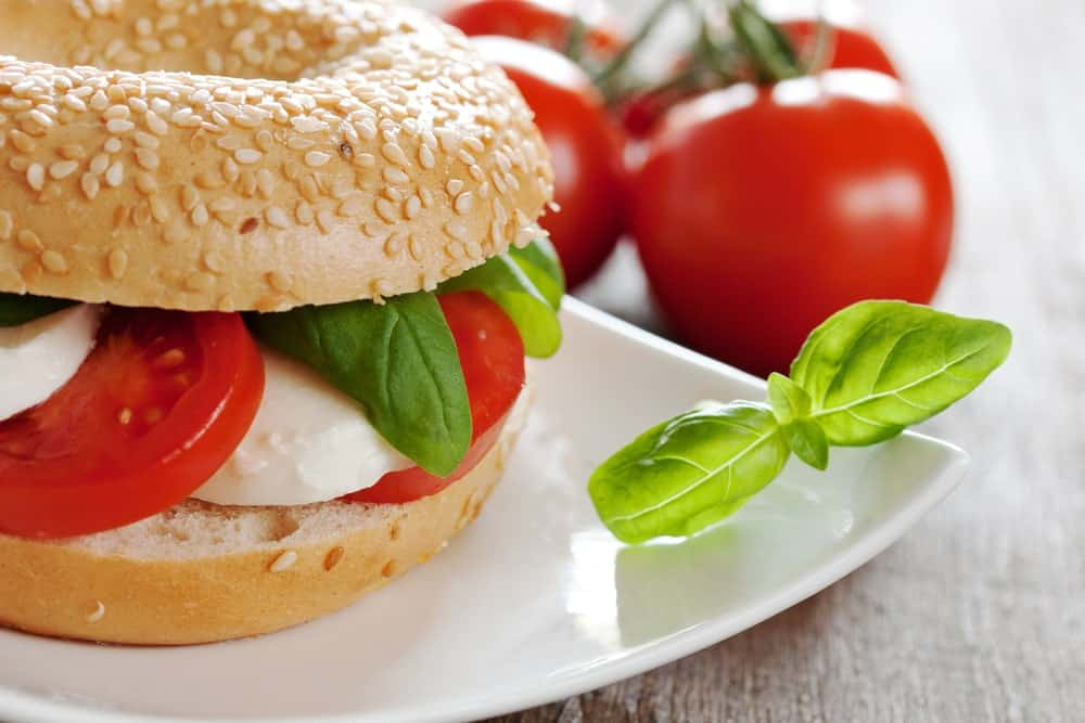 A plate of bagel sandwich with tomato and cheese beside fresh tomatoes.