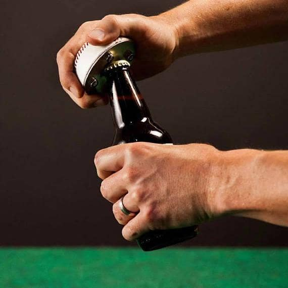 Opening a bottle of beer using a handmade bottle opener.