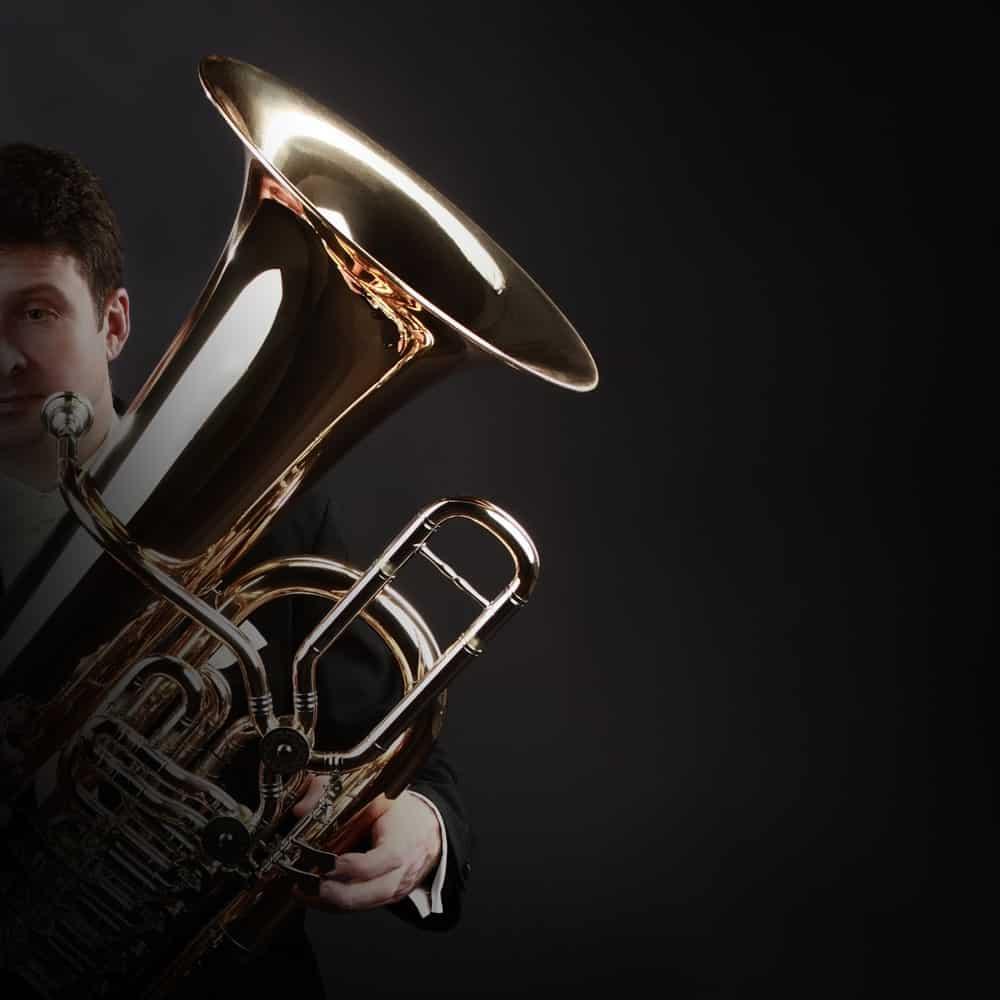 Musician holding a bass tuba.