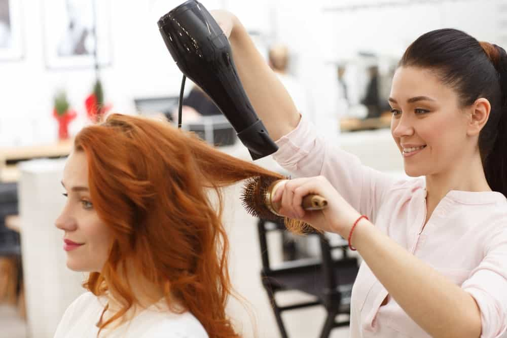 Ginger-haired woman getting a blow dry from her stylist.