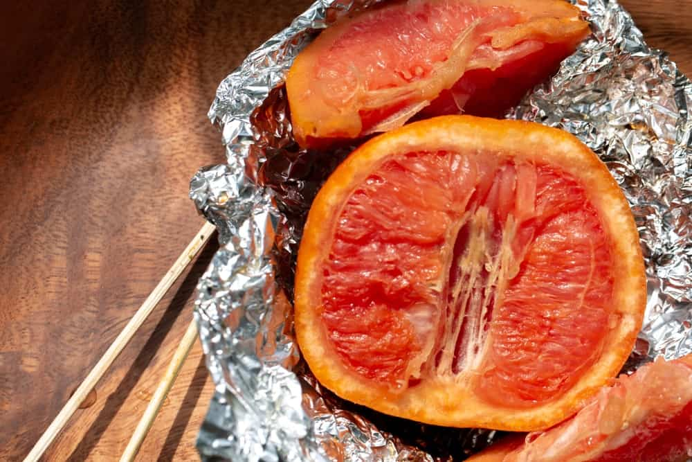 Slices of broiled grapefruit in a tin foil on wooden background.