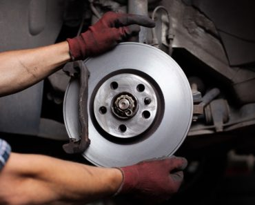 A mechanic is repairing a car brake.